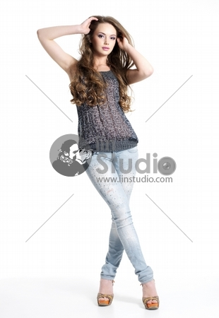 Beautiful and sexy young girl in casual clothes posing - isolated on white. Fashion model posing at studio