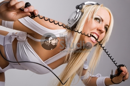 Excited blond model biting headphones cable