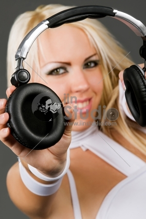 Excited blond model in futuristic style clothes with headphones