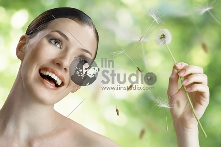beautiful smiling girl with dandelion in hand