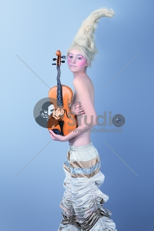 Portrait of an artistic young woman posing with violin. Shot in a studio.