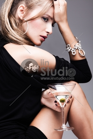 young fashion woman with glass of martini, profile, studio shot