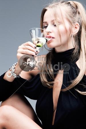 blond woman drinking martini, studio shot