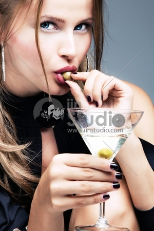 young woman with glass of martini and olive in mouth, studio shot
