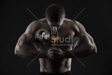 strong athletic man with a flower