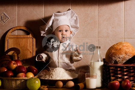 little boy in the cook costume at the kitchen sitting on the table. Special toned photo f/x