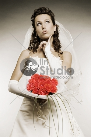 thoughtful bride with bunch of flowers over grey background