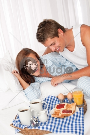 Young man and woman having breakfast together in white bed