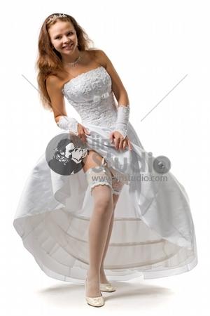beautiful bride in a wedding dress shows a garter on a foot