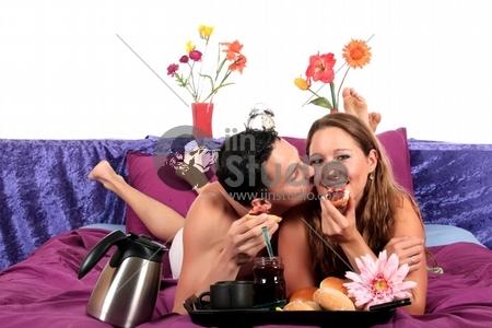 young loving couple having breakfast on bed. Studio.