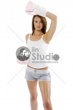 Close Up Of A Young Attractive Woman Wearing Pink Boxing Gloves Holding A Blocking Position Isolated On A White Background.
