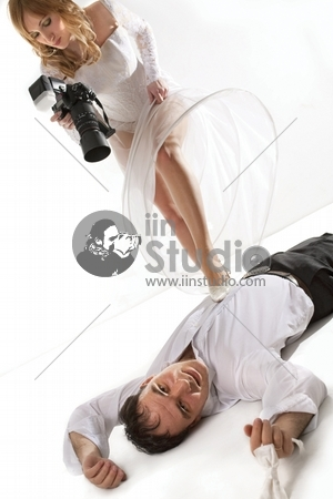 Bride taking picture of her groom laying on floor