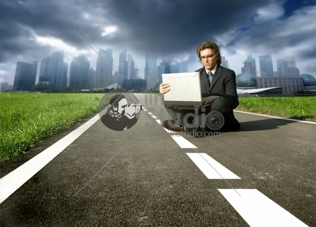 a business man on the street with a laptop