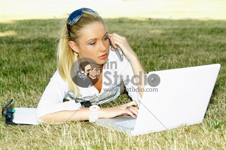 Business woman working on grass with laptop computer