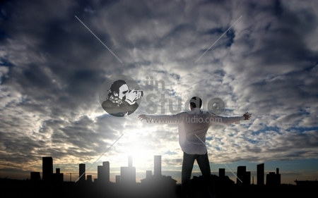 man with open arms facing a city's silhouette at the sunset