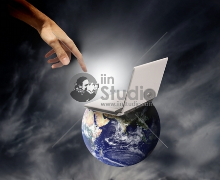 an hand touching a laptop leaning on the planet earth