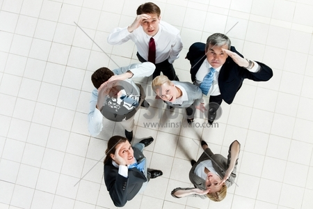 Portrait of confused business group standing on the floor and looking at camera