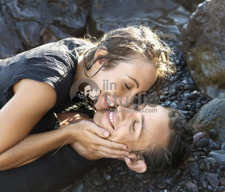 Attractive young couple smile with closed eyes while lying on a rocky shore. Vertical shot.