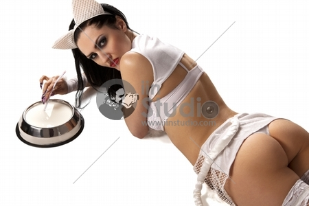 Hot beautiful model in latex white cat costume drinking milk from cat bowl