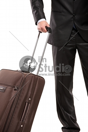 Business traveller with a suitcase isolated on white background (focus on the suitcase)