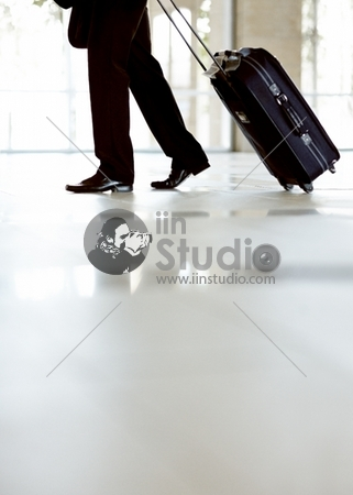 Lower Section Of A Male Business executive Walking With Travel Bag