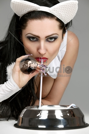 Portrait of beautiful model in latex white cat costume drinking milk from cat bowl