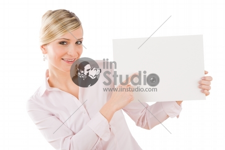 Happy businesswoman pointing aside at blank advertising banner on white