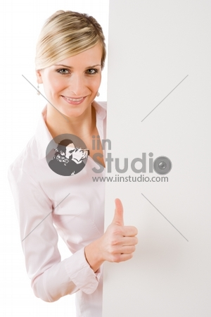 Happy business woman behind blank advertising banner thumbs up