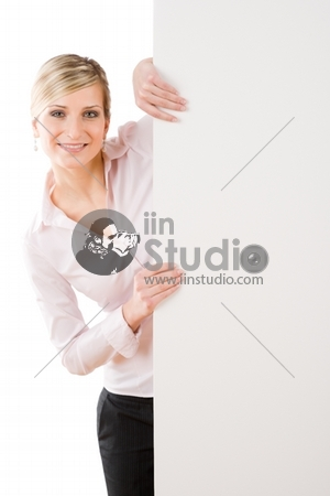 Happy businesswoman behind blank advertising banner standing