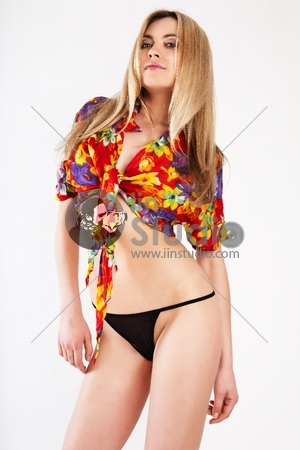 Young woman standing in a colorful shirt and black underpants