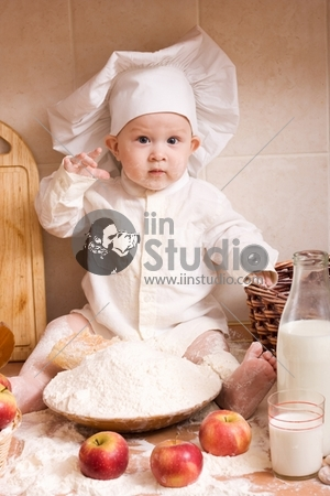 little boy in the cook costume at the kitchen