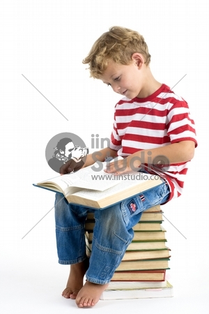 Five year old boy sitting on pile of books, reading