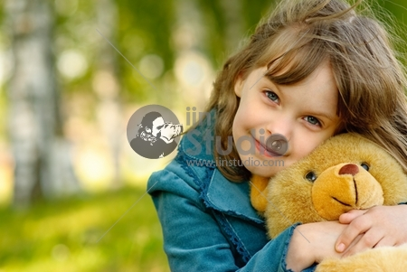 Small beautiful girl embraces an amusing bear cub against summer nature.