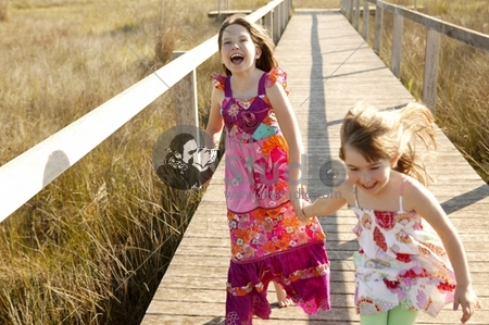 Teen two girls running outdoor at the park, hippie pink dress (focus on the tall one)