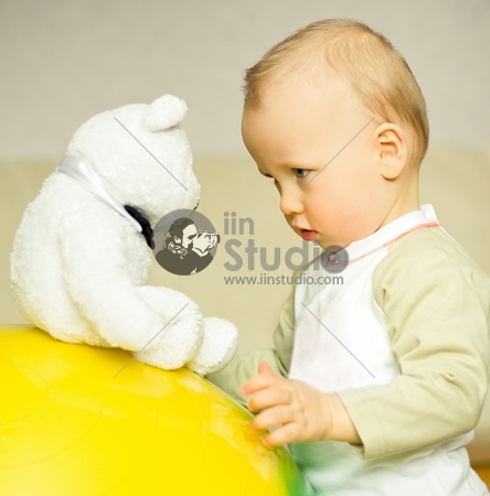 boy looks at bear toy
