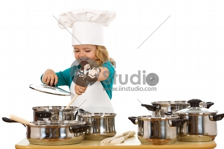 Happy chef girl stirring soup in a bowl
