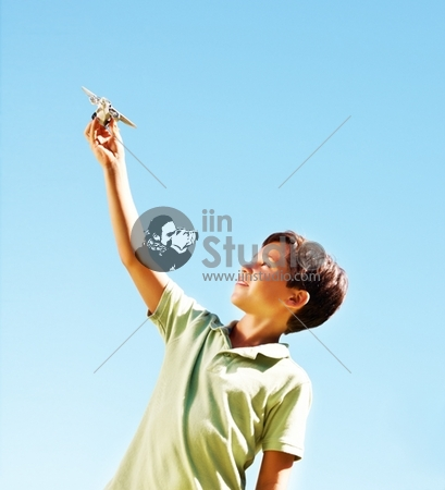 Happy Young Boy With A Toy Plane Against The Clear Blue Sky