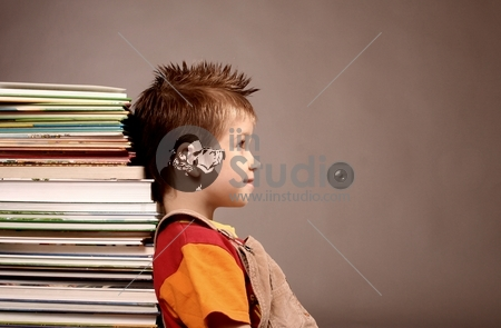 A Little Kid With Books Is Smiling