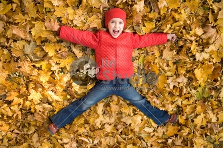 Above view of excited child shouting from happiness while lying on dry autumnal leaves
