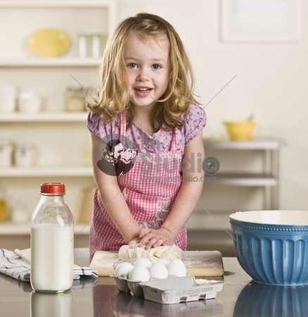 Cute blond little girl making bread in the kitchen. Milk bottle, bowl and eggs on the counter. Square