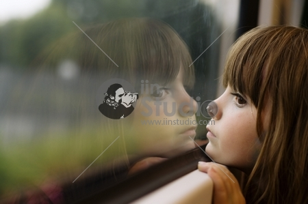 Little Girl Looking Through Window With Reflections Showing As She Travels Through The Countryside On A Train.