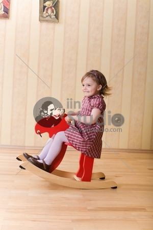 Happy little girl play with toy wooden deer