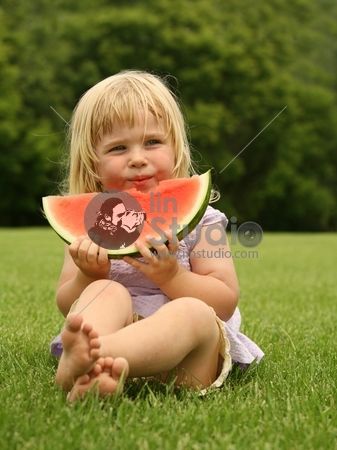 adorable little toddler sitting on the grass with a piece of watermelon