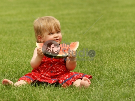 adorable little baby sitting on the grass with a piece of watermelon