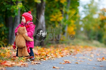 Cute 1 year old girl walking outdoors at autumn day