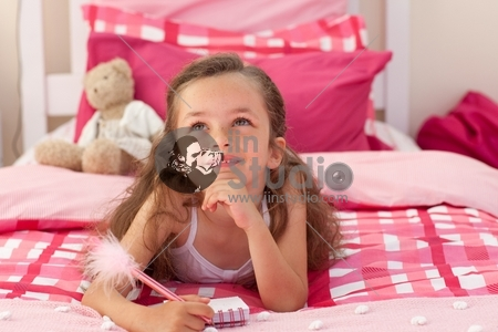 Smiling girl writing and lying on bed