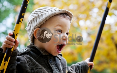 excited toddler on a swing outdoors, autumn leaves in background