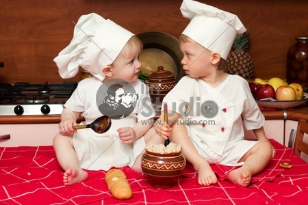 two little babies in the cook costumes at the kitchen sitting on the table
