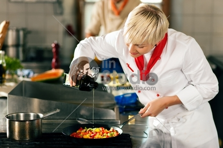 Two chefs in teamwork - man and woman - in a restaurant or hotel kitchen cooking delicious food, she is putting olive oil in the ratatouille