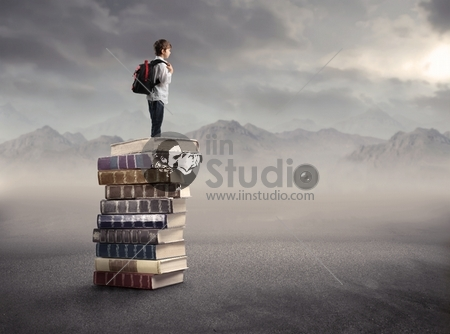 Child with rucksack standing on a stack of books